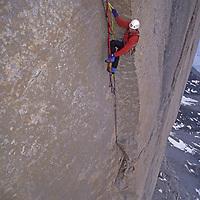 BAFFIN ISLAND, Nunavut, Canada. Alex Lowe aid climbs high on Great Sail Peak, an Arctic big wall rock climb above frozen lake in Stewart Valley.