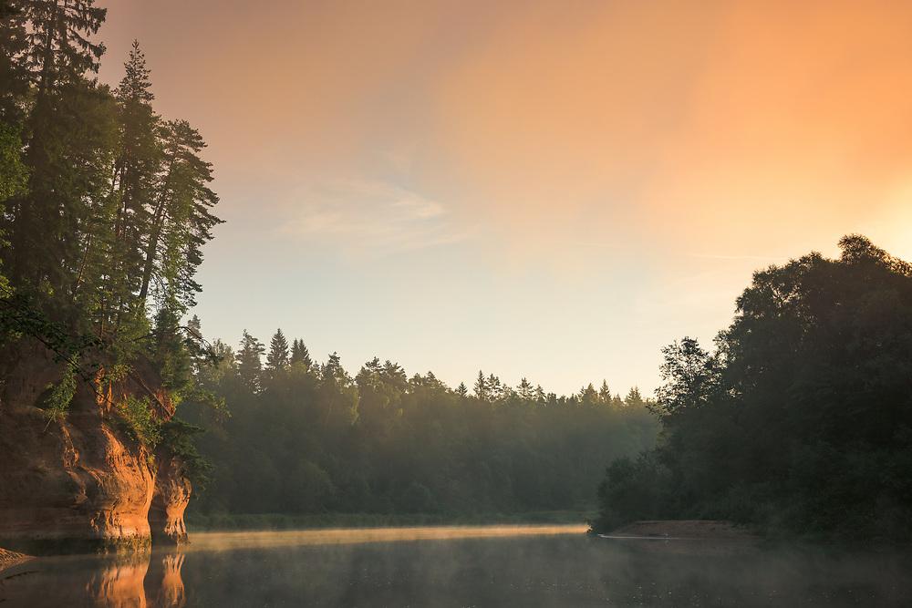 Warm light from rising sun exposes the colorful sandstone cliffs and fog covered River Gauja, Gauja National Park (Gaujas Nacionālais parks), Latvia Ⓒ Davis Ulands | davisulands.com