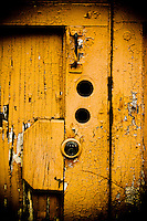 The rustic nature of an old garage door with the cracked paint and multiple cut-outs for locks conveys years of use and neglect.