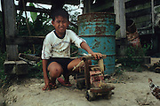 LOGGING, MALAYSIA. Sarawak, Borneo, South East Asia. Logging camp. Boy with home-made toy logging truck. Tropical rainforest and one of the world's richest, oldest eco-systems, flora and fauna, under threat from development, logging and deforestation. Home to indigenous Dayak native tribal peoples, farming by slash and burn cultivation, fishing and hunting wild boar. Home to the Penan, traditional nomadic hunter-gatherers, of whom only one thousand survive, eating roots, and hunting wild animals with blowpipes. Animists, Christians, they still practice traditional medicine from herbs and plants. Native people have mounted protests and blockades against logging concessions, many have been arrested and imprisoned.