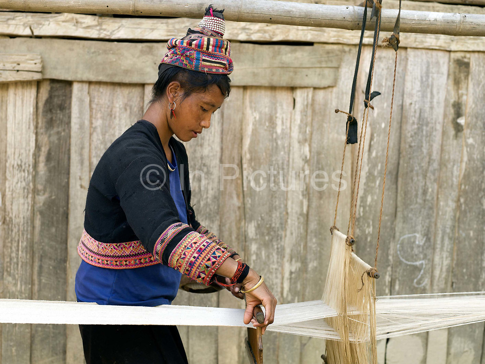 A Ko Pala woman weaves home grown, organic cotton fabric on a basic loom outside her home in Ban Lao Li, Phongsaly Province, Lao PDR.  In some areas, Pala women still grow, gin and spin cotton into thread and set up their looms outdoors for weaving cotton. One of the most ethnically diverse countries in Southeast Asia, Laos has 49 officially recognised ethnic groups although there are many more self-identified and sub groups. These groups are distinguished by their own customs, beliefs and rituals. Details down to the embroidery on a shirt, the colour of the trim and the type of skirt all help signify the wearer's ethnic and clan affiliations.