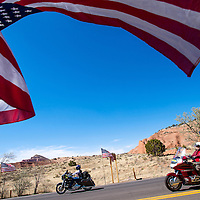051613       Cable Hoover<br /> <br /> Riders are greeted with a flag-lined avenue as they enter Red Rock Park in Gallup for the reception of Run for the Wall veteran's memorial motorcycle ride Thursday.