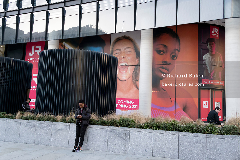 Three Londoners look at messages beneath a large billboard featuring an ecstatic young woman, on the exterior of a soon-to-open fitness club opposite Liverpool Station in the City of London, the capital's financial district, on 26th February 2021, in London, England.