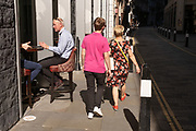 Two women walk past a city worker sitting on a bar stool outside a pub on Throgmorton Street during the Coronavirus pandemic in the City of London, the capital's financial district, on 30th July 2020, in London, England.
