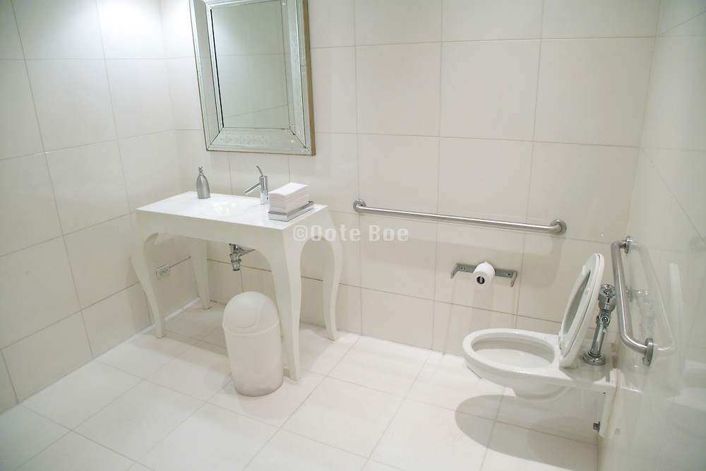 a very large white public toilet room