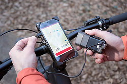 Mountain biker connecting GPS gear with external battery charger, Trentino, Italy