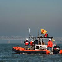 Workmen cross San Francisco Bay in a motorized commercial raft. Behind is the Bay Bridge.