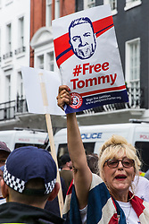 London, UK. 10th June, 2018. A woman holds up a poster calling for the release from jail of Tommy Robinson, former leader of the English Defence League, as she protests with members of far-right groups against the pro-Palestinian Al Quds Day march through central London organised by the Islamic Human Rights Commission. An international event, it began in Iran in 1979. Quds is the Arabic name for Jerusalem.