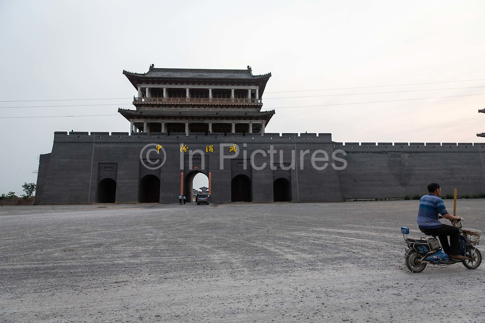 A man rides his scooter past the gates of a baijiu liquor distillery city, made in imitation of a traditional Chinese city,  in Liulin, Shanxi province, China, on Thursday, May 19, 2016. Shanxi is facing a challenge shared by a sweeping region across Chinas industrial north: how to shut down cash-burning mines that employ millions of people whose prospects are uncertain in the new economy promised by President Xi Jinping. New business ventures like the distillery city, funded by coal money with grandiose hopes and expectations, often prove too ambitious and unrealistic.