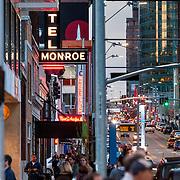 Vertical photo of crowded city street; sidewalk and road traffic; Main Street, downtown Kansas City, Missouri.