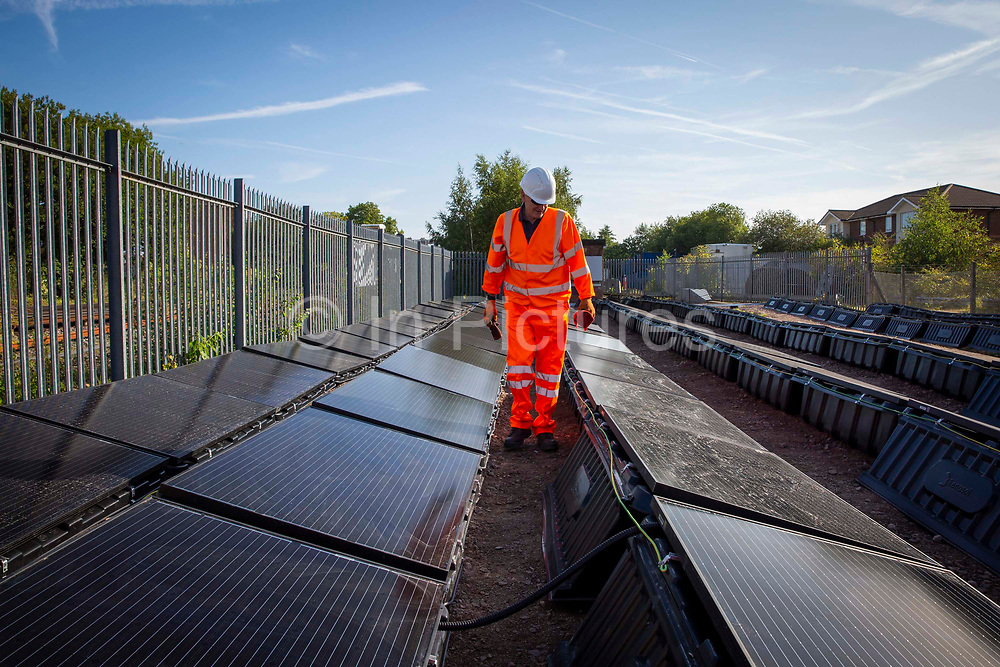 An array of solar panels next to the line near Aldershot Railway Station on 23rd August 2019 in Aldershot, United Kingdom. This innovative project is the first in the UK to power the railway with electricity generated from solar power and, if successful, could see many Network Rail sites across the country adapting this sustainable energy approach. Riding Sunbeams is a social enterprise, run by 10:10 Climate Action. Built with Community Energy South and partnered with Network Rail and The Department for Transport and by InnovateUK.  Aldershot, Hampshire, United Kingdom. Riding Sunbeams is a world leading project to connect solar panels directly into electrified rail routes to power the trains. Direct supply of solar power to rail traction systems has never been done. But it has huge potential - from metros, trams and railways in the UK and around the world.