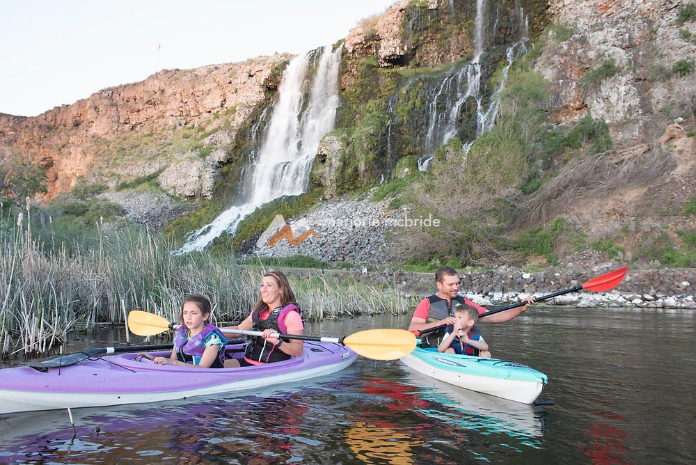Family kayaking below Thousand Springs waterfall at Ritter Island in the Snake River Hagerman, Idaho. MR