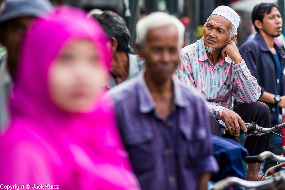 09 JULY 2013 - PATTANI, PATTANI, THAILAND: A Muslim pedicab driver waits for a fare in the market in Pattani.  Pattani, along with Narathiwat and Yala, are the only three Muslim majority provinces in Thailand.     PHOTO BY JACK KURTZ