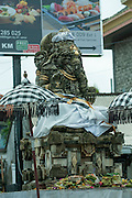 Old statue of Ganesha with very modern billboards behind.<br /> Sanur, Bali