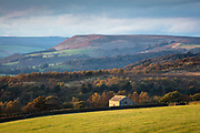 Early evening on a stunning autumnal day in the Peak District National Park. Sunlight illuminates Longshaw Barn in the foreground, with a backdrop of colourful woodland and Bamford Edge in the distance. A classic Derbyshire scene, England, UK