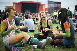 © London News Pictures. 24/08/2012. London, UK. A group of three girls applying body paint to themselves in front of the main stage on day one of Reading Festival 2012 in Reading, Berkshire, UK on August 24, 2012. The three day event which attracts over 80,000 music fans opens officially today (Friday) and will headline The Cure, Kasabian and The Foo Fighters Photo credit : Ben Cawthra/LNP