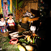 A pair of children in Anitgua, Guatemala, pose for photos in costume with a traditional scene in the background. This was part of a market in downtown Antigua in celebration of a national holiday.