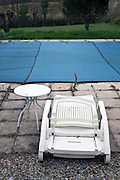 closed up swimming pool with folded plastic reclining chair and table