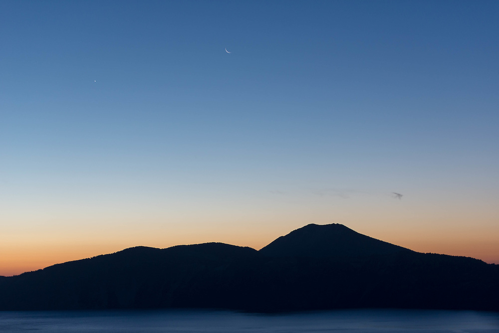 The Sliver Moon and Venus rest above Crater Lake in the early morning