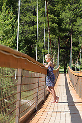 girl on a foot bridge looking alone