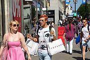 Shopper with Topshop bags wearing heart shaped sunglasses as the Coronavirus lockdown measures are set to ease further, the west end starts to fill with people as they return to the shopping district on Oxford Street and the quiet city starts coming to an end on 22nd June 2020 in London, England, United Kingdom. As of today the government has relaxed its lockdown rules, and is allowing some non-essential shops to open with individual shops setting up social distancing queueing systems.