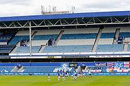 Queens Park Rangers players warming in front of empty stands up before the EFL Sky Bet Championship match between Queens Park Rangers and Barnsley at the Kiyan Prince Foundation Stadium, London, England on 20 June 2020.