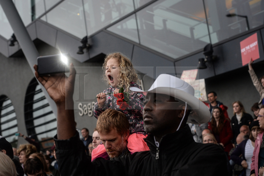 © Licensed to London News Pictures. 05/06/2017. Newcastle Upon Tyne, UK. A little girl holding a red rose is unable to stifle a yawn as she listens to Jeremy Corbyn MP, Leader of the Labour Party, after she waited with a crowd of hundreds, in the rain to hear him speak outside the Sage in Gateshead. Mr Corbyn spent one of the final days of the campaign trail in the Labour heartlands of North-East England before voters go to the polls in the UK General Election on June 8th 2017. Photo credit: MARY TURNER/LNP