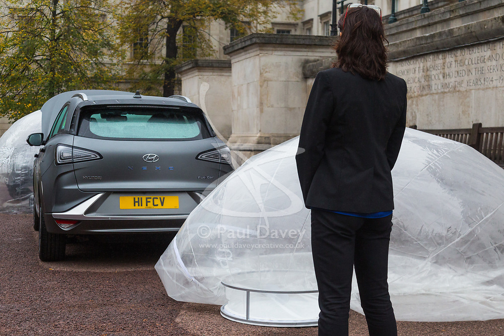 Sylvie Childs, Senior Product Manager at Hyundai UK watches as a balloon fed by the exhaust inflates with completely clean air as Hyundai UK demonstrates the Hydrogen-powered Nexo that not only produces completely clean emissions but also cleans up the air its engine ingests, thanks to a filtration system developed by scientists at University College London. UCL London, October 17 2018.