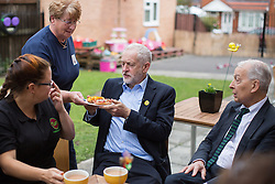 © Licensed to London News Pictures . 24/09/2016 . Liverpool , UK . JEREMY CORBYN eats pizza breads he made during a visit to Beaconsfield Community House in Birkenhead , following his victory declaration . The centre provides clothes and food that would otherwise be destined for waste from supermarkets , to local residents in need . Photo credit : Joel Goodman/LNP