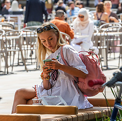 © Licensed to London News Pictures. 22/07/2020. London, UK. A young shopper enjoys the warm sunshine on the King's Road in Chelsea as weather forecasters predict 26c today as Londoners get ready for Friday when masks become compulsory in shops in England. Photo credit: Alex Lentati/LNP