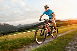 Mountainbiker rides at sunset in alps,, Bavaria, Germany