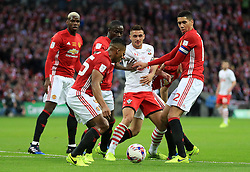 Southampton's Dusan Tadic (centre) battles for the ball with Manchester United defence players during the EFL Cup Final at Wembley Stadium, London.