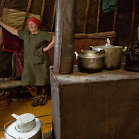 North of the Arctic Circle in Russia, 77-year old Marie Terentéva, a member of the last nomadic Komi reindeer herding clan, relaxes by the wood stove in her cozy chum (tepee), which is much warmer than sub-freezing temperatures outside.