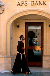 MALTA GOZO VICTORIA JUL00 - A Jesuit monk passes the APS Bank building in Victoria.. . jre/Photo by Jiri Rezac. . © Jiri Rezac 2000. . Tel:   +44 (0) 7050 110 417. Email: info@jirirezac.com. Web:   www.jirirezac.com