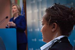 A female member of Hillary Clinton's security detail keeps watch while  Clinton speaks in the United Arab Emirates, Jan. 10, 2011.