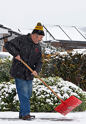 © Licensed to London News Pictures 09/02/2021.        Bromley, UK. A man clearing his pathway from overnight snow. The snow continues to fall in the Borough of Bromley, South East London today. Weather warnings remain in place across the UK for more freezing cold snowy weather. Photo credit:Grant Falvey/LNP