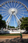 People passing a ferris wheel in Hyde Park, London. Here some very traditional fairground rides were operating for tourists and local people alike giving a feeling of old fashioned fun in it's most simple way.