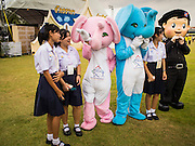02 DECEMBER 2014 - BANGKOK, THAILAND: High school students play with mascots promoting tourism before the Trooping of the Colors, at a celebration of the King's Birthday. The Thai Royal Guards parade, also known as Trooping of the Colors, occurs every December 2 in celebration of the birthday of Bhumibol Adulyadej, the King of Thailand. The Royal Guards of the Royal Thai Armed Forces perform a military parade and pledge loyalty to the monarch. Historically, the venue has been the Royal Plaza in front of the Dusit Palace and the Ananta Samakhom Throne Hall. This year it was held on Sanam Luang in front of the Grand Palace.    PHOTO BY JACK KURTZ