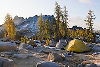 A woman emerges from her tent in the Enchantment Lakes Wilderness Area, Washington Cascades, USA.