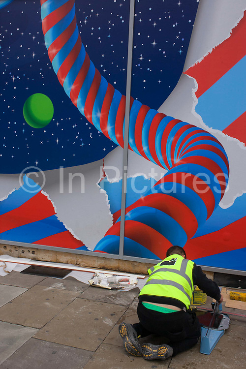 A workman in a hi-viz tabard bends down in front of the window screen, an essential job for a forthcoming The Toy Store shop in Oxford Street, central London. In the background are the bright colours of a construction hoarding for a new Toy Store on this busy street in Westminster, central London. There is a theme of striped poles and twisting design that helps lure the young and seduce their business when open soon.