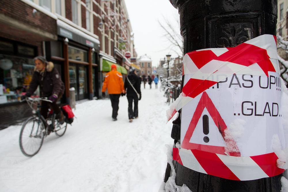 Een plakaat bij de Vismarkt in Utrecht waarschuwt voor gladheid. De hevige sneeuwval in Nederland heeft voor de nodige problemen gezorgd in het land.<br /> <br /> A sign at the Vismarkt in Utrecht is warning for slipperiness.