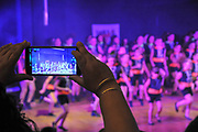 Woman uses cellphone to record a video of primary school graduation ceremony