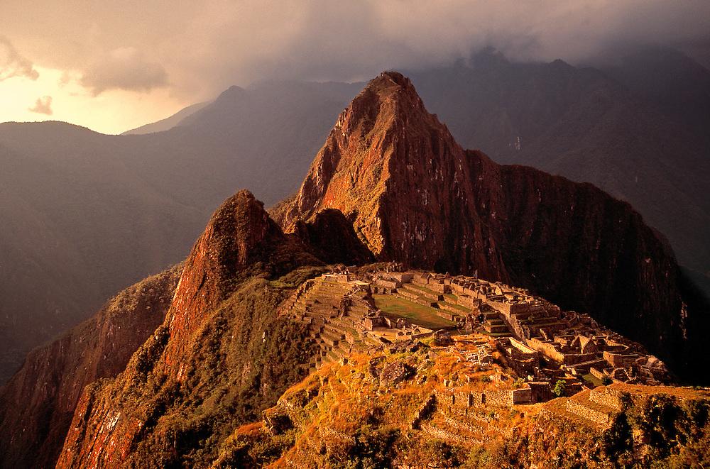 Sunset light breaks through storm clouds to cast a warm glow over the Inca ruins of Machu Picchu, Peru.