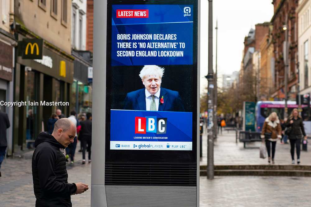 Glasgow,Scotland, UK. 2 November 2020. As Scotland enters new Coronavirus lockdown regulations the central belt and Glasgow are placed in Level 3 . Members of the public are seen out on the streets of central Glasgow for shopping and work. Pictured; Video screen shows news headlines with Boris Johnson declaring no alternative to second England lockdown. Iain Masterton/Alamy Live News