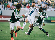 Los Angeles Galaxy midfielder David Beckham, middle, makes a pass around Portland Timbers midfielder Franck Songo'o, right, as Portland Timbers defender Mike Chabala, left, gives chase during the first half of an MLS soccer match, Sunday, June 17, 2012, in Carson, Calif. (AP Photo/Bret Hartman)