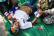 """09 DECEMBER 2013 - BANGKOK, THAILAND:  Medics tend to an anti-government protestor who collapsed in the heat in front of Government House in Bangkok Monday. Thai Prime Minister Yingluck Shinawatra announced she would dissolve the lower house of the Parliament and call new elections in the face of ongoing anti-government protests in Bangkok. Hundreds of thousands of people flocked to Government House, the office of the Prime Minister, Monday to celebrate the collapse of the government after Yingluck made her announcement. Former Deputy Prime Minister Suthep Thaugsuban, the organizer of the protests, said the protests would continue until the """"Thaksin influence is uprooted from Thailand."""" There were no reports of violence in the protests Monday.     PHOTO BY JACK KURTZ"""