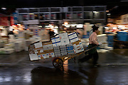Aworkers pulls a cart loaded with boxes at Tsukiji whiolesale fish market as it reopens to tourists after being closed for one month. Tsukiji is the largest wholesale fish market in the world and a major tourist attraction in Tokyo. But visitor numbers have increased to a level now that is affacting the day to day running of the market and severe restrictions have been placed on the movement of tourists at its busiest time. Tsukiji, Tokyo, Japan. May 10th 2010