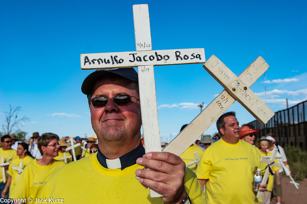 17 APRIL 2005 - NACO, AZ: Progressive Christians, some holding crosses bearing the names of migrants who died crossing the border, on the US side of the US/Mexico border march to the border in Naco, AZ to support migrants' rights. The Christians had gathered to protest the presence of the  Minuteman Project in Naco. The Minuteman volunteers were hunting migrants who crossed the border outside of Naco.      PHOTO BY JACK KURTZ