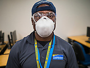 """19 MARCH 2020 - DES MOINES, IOWA:  SAM TEAH, a worker for the Des Moines Public Schools, wearing protective gear to clean a classroom at Central Campus, a high school in the Des Moines Public Schools system. Des Moines schools are closed for at least 30 days because of the coronavirus and officials are using the time to """"deep clean"""" and sanitize each school. On Thursday morning, 19 March, Iowa reported 38 confirmed cases of the Coronavirus. Restaurants, bars, movie theaters, places that draw crowds are closed for at least 30 days. There are no """"shelter in place"""" orders in effect anywhere in Iowa but people are being encouraged to practice """"social distancing"""" and many businesses are requiring or encouraging employees to telecommute.        PHOTO BY JACK KURTZ"""
