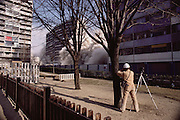 Controlled Demolition, Inc, used explosives to demolish an aging housing project near Paris. The Loizeaux brothers run the world's most famous demolition company founded by their father. Mark Loizeaux films and watches the demolition as his brother Doug pushes the detonation controller. La Courneuve, France. Second in a series of three photos.
